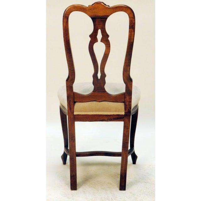Elegant carved upholstered side chair.