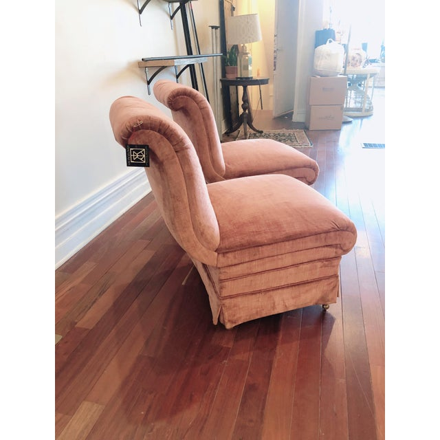 Darling pair of pink, curvaceous slipper chairs upholstered in cotton velvet. Featuring a wheeled base for ease of...