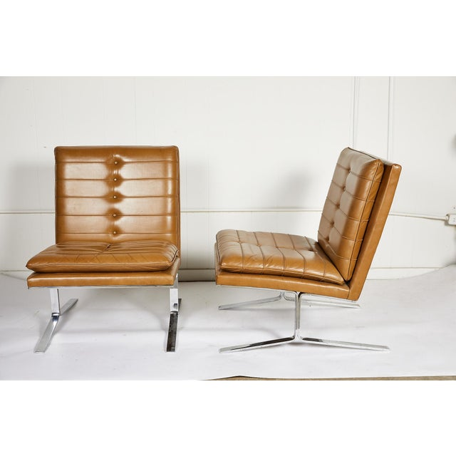 Stylish pair of American midcentury armless lounge chairs with channeled camel leather seats and backs, on bright chrome...