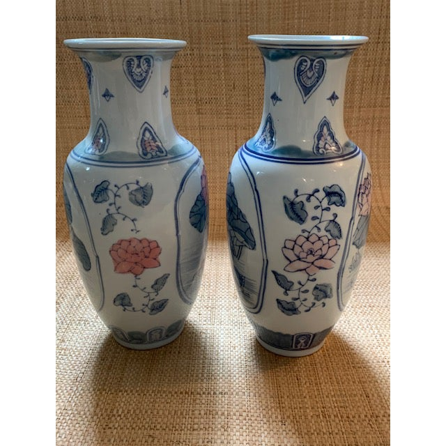 Tall pair of porcelain vases with lotus flowers and birds. Hand painted in soft blue, pink and green. Great flanking a...