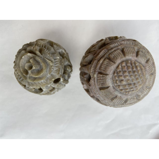 A pair of hand carved eggs. Inside are small owls peering out. The larger egg has a sunflower carved into the top and the...