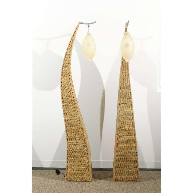 An Unusual pair of vintage large scale modern floor lamps, circa 1980's. Woven raffia over a metal frame. Highly...