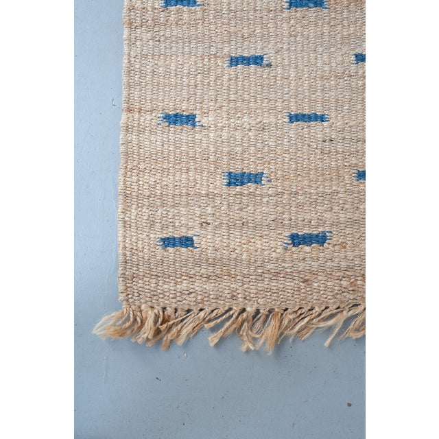 Woven jute rug with fringe and dashed blue motifs