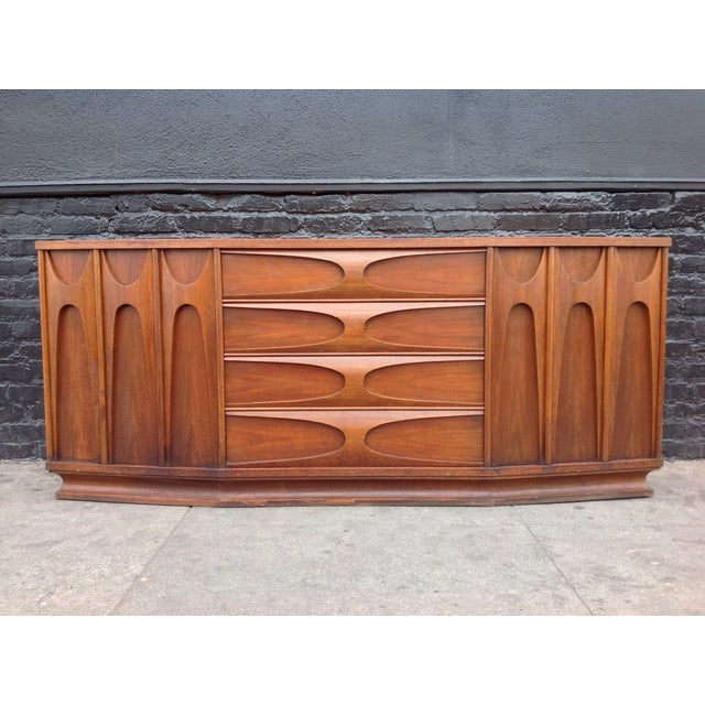A stunning credenza piece by K-Wee & Co. This credenza has an angular design on the front with a beautiful Broyhill...