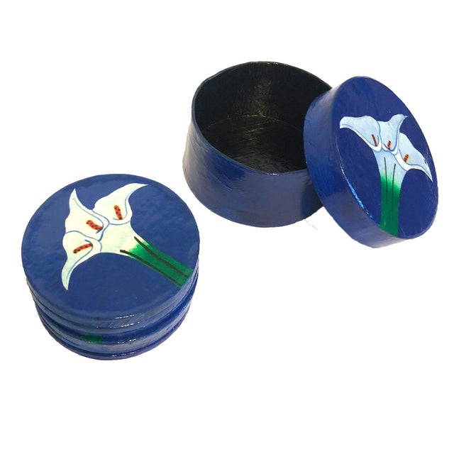 Vintage hand-painted papier-mâché coaster set. The coasters feature painted calla lilies against a blue background. Set of...