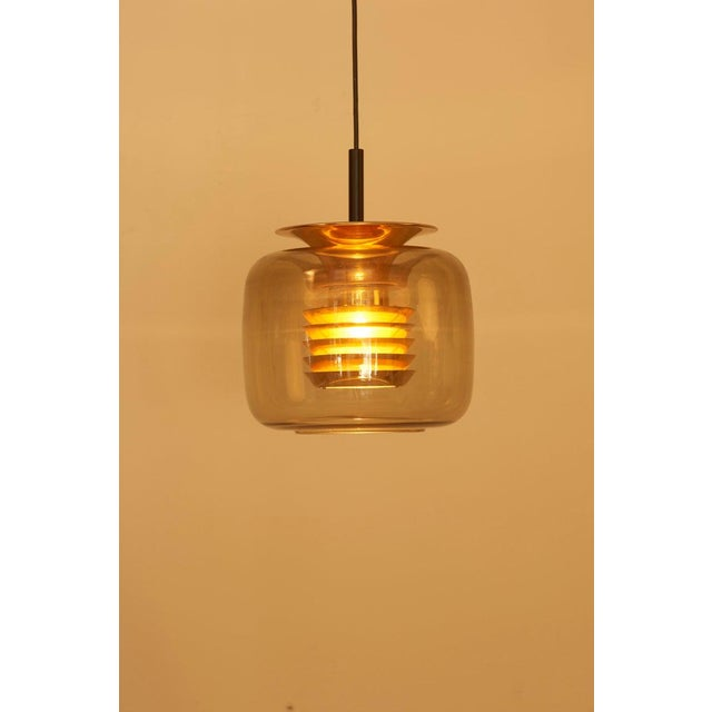 Pendant lamp with glass and brass in manner of Hans-Agne-Jakobsson. 1 x E27 bulb. To be on the safe side, the lamp should...