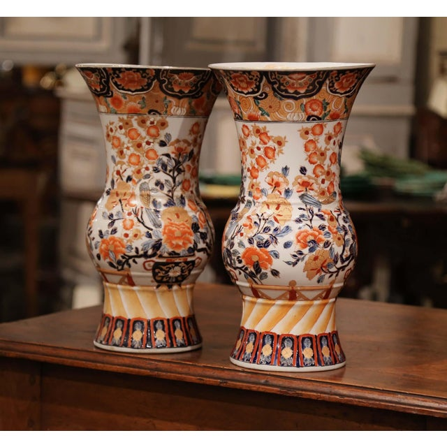 These tall antique porcelain Imari vases were created in Japan circa 1920. Each ceramic vessel has a wide mouth at the...