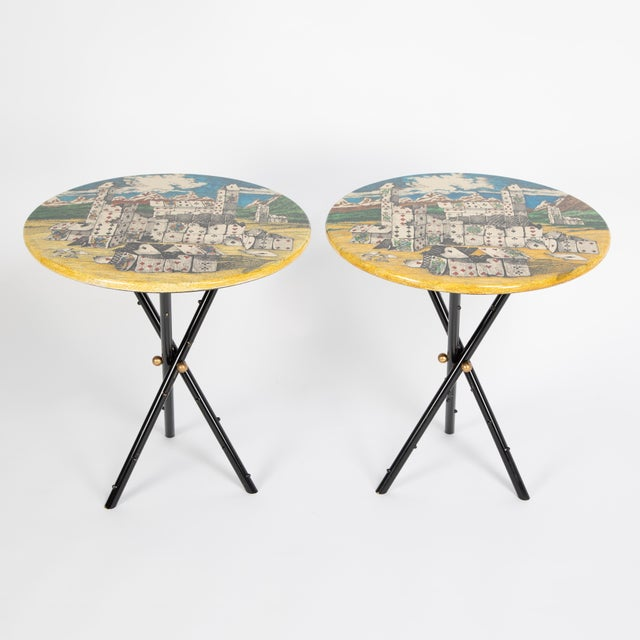 Whimsical pair of 1950s Piero Fornasetti side tables feature black-painted-brass tripod bases with tops adorned with...