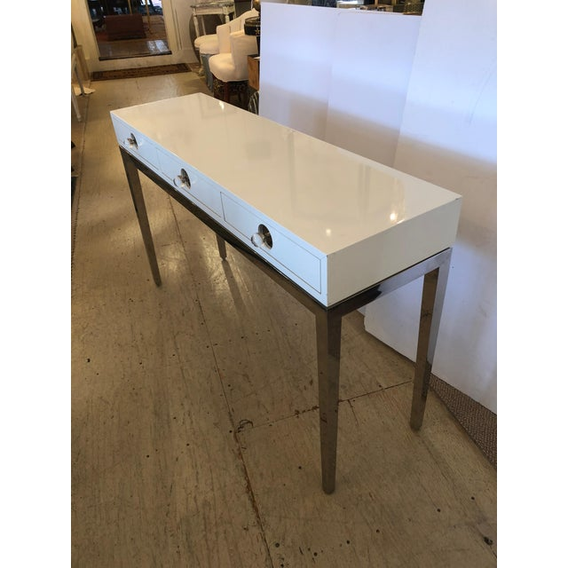 A mod version of midcentury design, this is a sleek contemporary console by Jonathan Adler having chrome base, elegant...