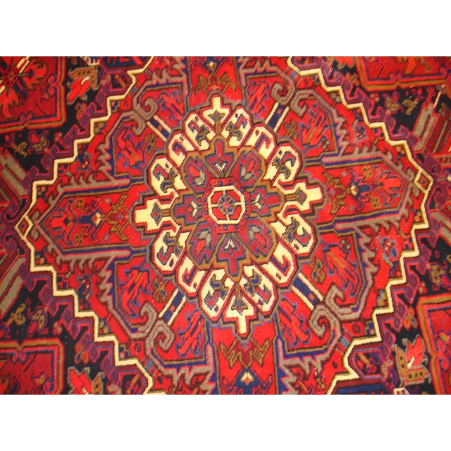 Nothing adds a timeless elegance to a space like a fine Persian Heriz area rug. This handmade piece features rich, vibrant...