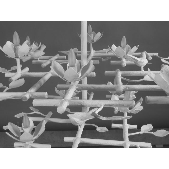 This garden chandelier has three tiered layers and has a white finish. Birds and flowers are detailed throughout. Plaster...