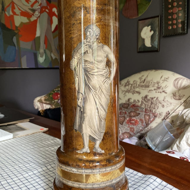 A stunning vintage table lamp in the style of Piero Fornasetti. The lamp is a cylinder glass urn shape with Greco-Roman...
