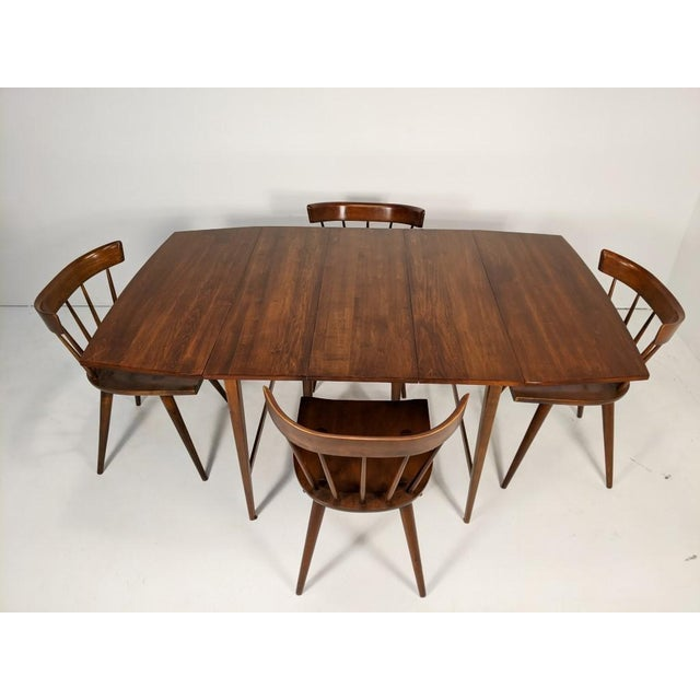 This exquisite mid century modern dining set from the drawing table of famed designer Paul McCobb is as rare and wonderful...
