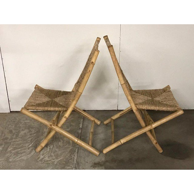 Pair of Faux bamboo campaign chairs, in the manner of Maison Jansen, Each one with rush back rests and seats, they fold...