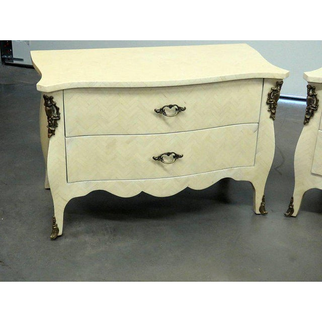 Pair of Enrique Garcia two-drawer commodes with faux bone veneer and bronze accents.
