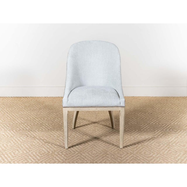 Upholstered dining low-arm chair. Platinum nail head trim. Oatmeal finish. Fabric: Ladd Seafoam 66% Polyester, 34%...