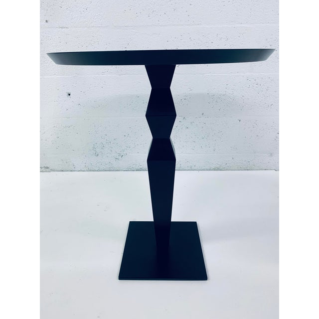 Christian Liaigre side or pedestal table in ebonized mahogany with black steel base for Holly Hunt.