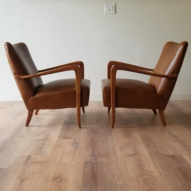 A pair of beautiful Mid-Century Modern Italian leather armchairs. These chairs have acquired a stunning patina on both the...