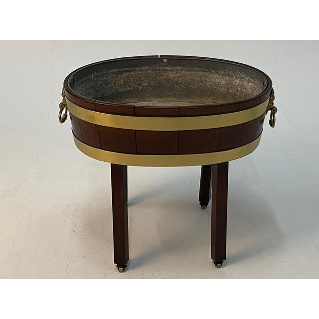 A beautiful antique English Georgian style oval mahogany cellarette on stand having handsome brass banding and figural...