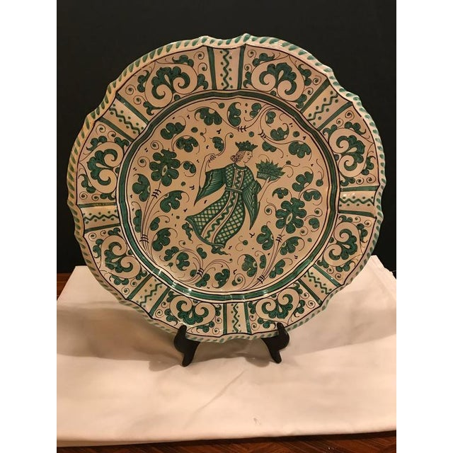 An Italian paint decorated platter. The back having a fire drilled pair of holds to mount this decorative platter to a...