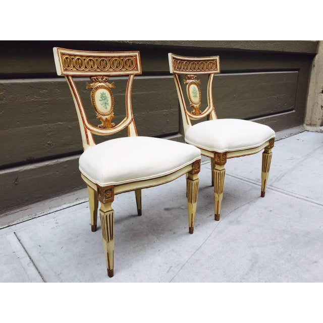 Pair of 19th century Italian neoclassical side chairs. Gold leaf and painted wood frame with linen upholstered seats.
