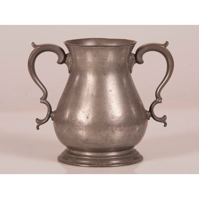 A large pewter urn with two shaped handles on the opposite sides of the vessel from England c.1850.