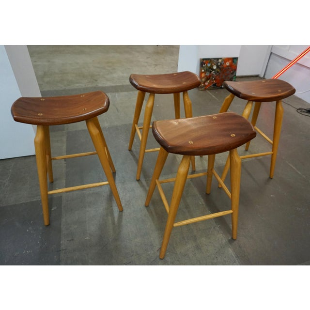 4 hand crafted bar or counter stools with walnut seats on oak legs.Interesting dowels attaching the seats to the bases.