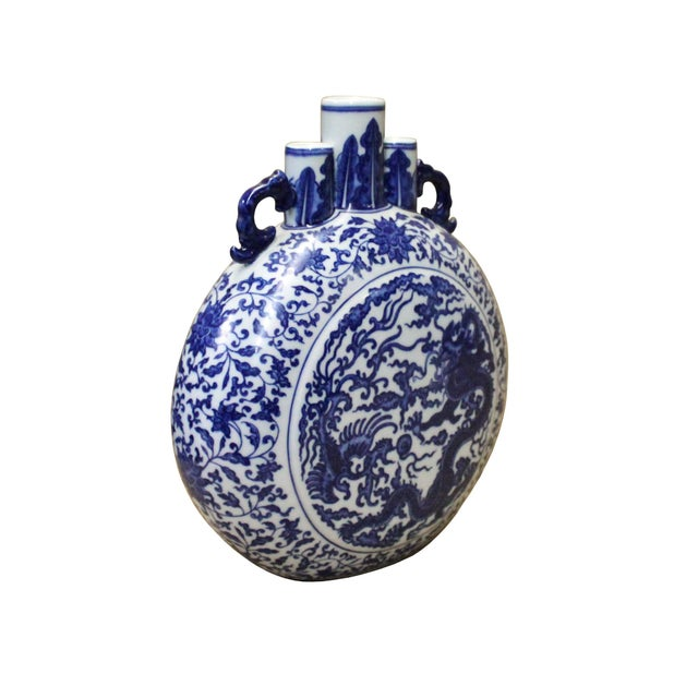 This is a Chinese decorative porcelain vase in Blue and White color finish. The theme is an oriental dragon phoenix...