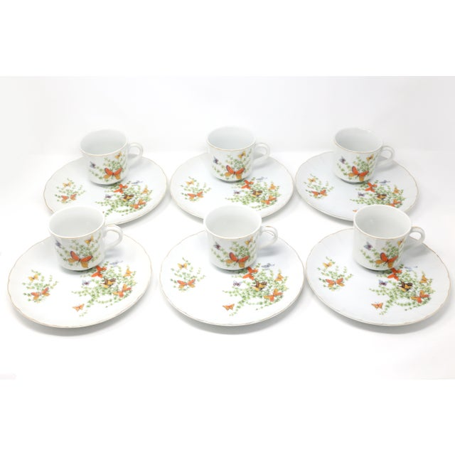 "A set of six porcelain snack plates and six cups, in the ""Ecstasy"" pattern by Shafford. Brightly colored orange, yellow..."
