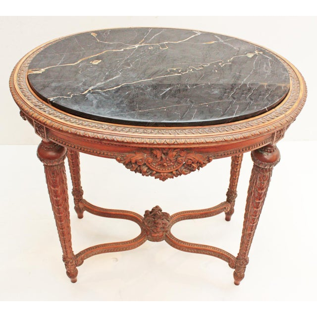 """An oval Art Deco era occasional table in the Louis XVI manner, fruitwood with heavily carved legs and apron, double """"U""""..."""