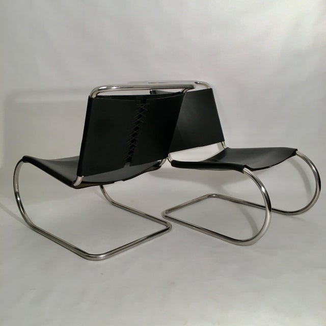 Pair of Mies Van der Rohe MR Lounge Chairs in Black Saddle Leather with polished stainless steel frames. No longer in...