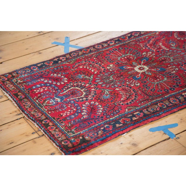 This rug features a diminutive center medallion with field comprised of floral bouquets and arrangements in bursting...