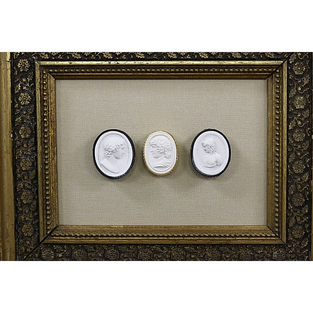 Set of three intaglios depicting Antinous mounted on beige silk in an antique frame. Each intaglio retains its original...