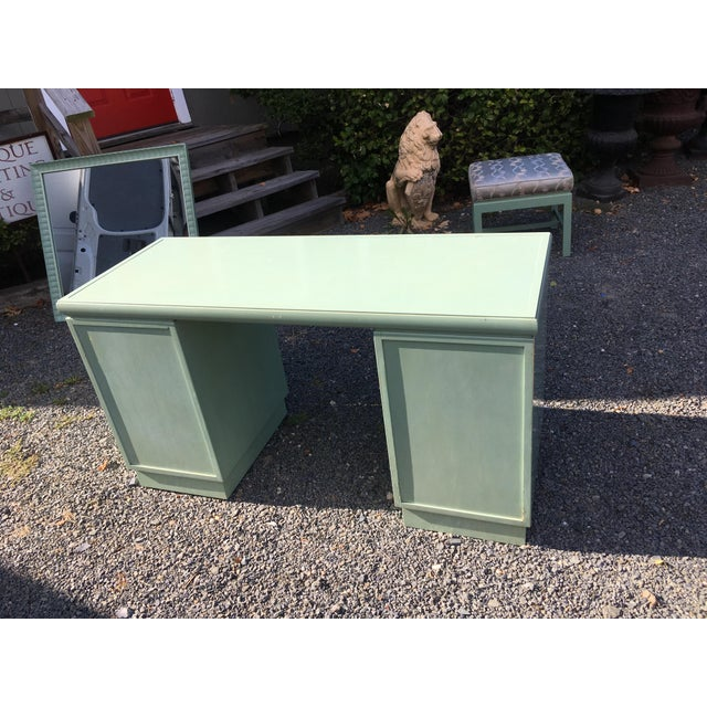 A glamorous painted vanity in seafoam green and white having stylish Greek key inspired pulls on the 3 stacked drawers...