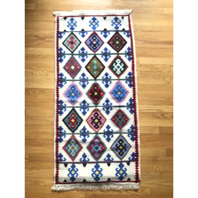Handmade rug with a diamond pattern. Cream background with red, blue, green, pink, tan, grey, teal, yellow, black and...