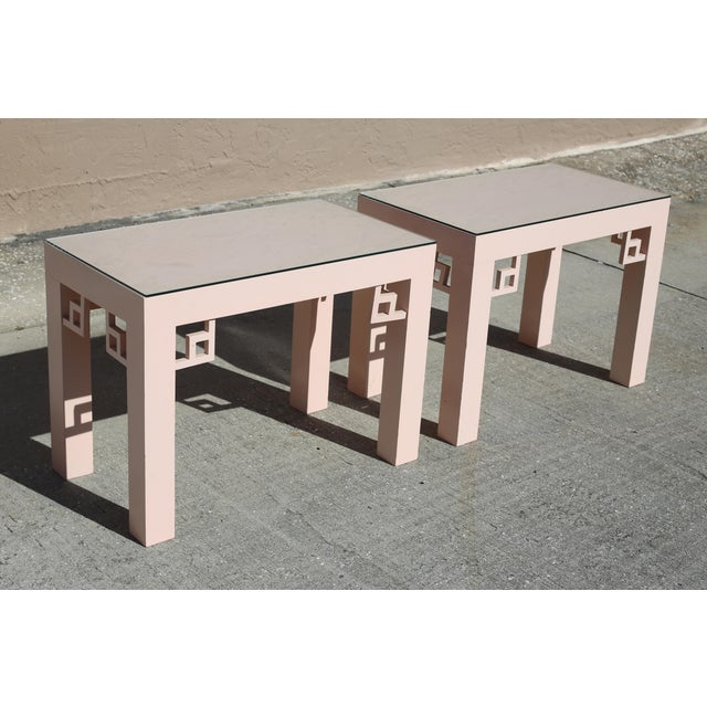 A pair of vintage, rectangular side tables, with blush-colored laminate, greek key-style corner accents, and glass tops....