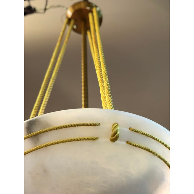 Neoclassical hanging light fixture with a decorative brass rope rod holding an alabaster bowl accented with gold silk...
