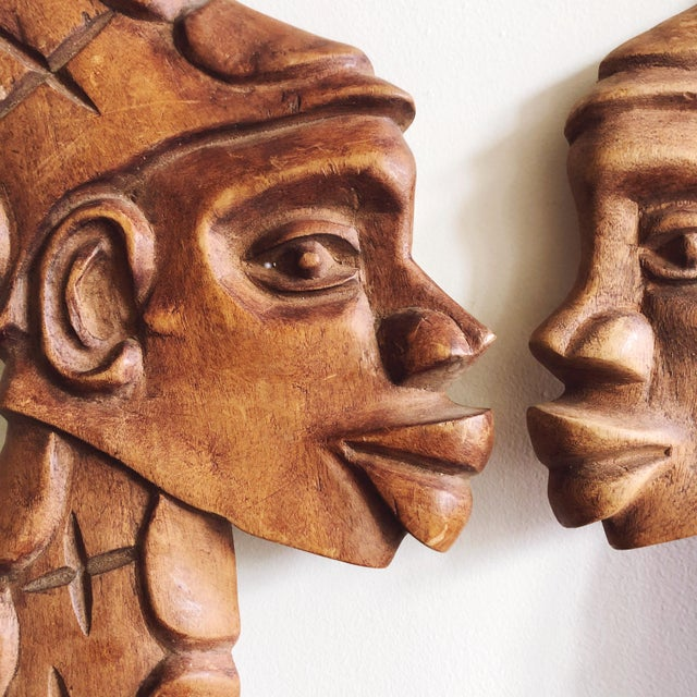 Vintage African art: carved wooden faces of a man and woman. A metal loop is attached to the back of each carving for...