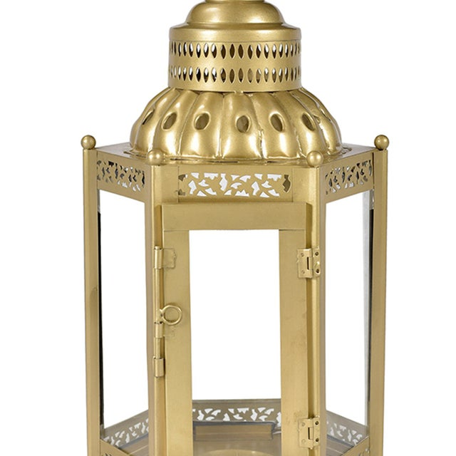 Brass finish iron work lantern. Intricate hand carved iron floral design with glass hinged door for candle.