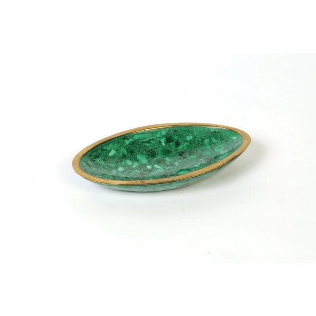 Delightful oval-shaped dish in vivid malachite stone with brass trim.