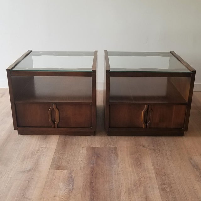 A pair of vintage walnut end tables. These side tables are very versatile by having a glass top which is great for plants...