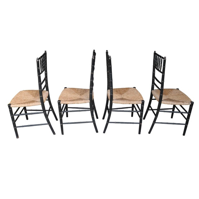 This set of four faux bamboo chairs are made of painted wood frames and rush seats. Slight patina and wear to the frames...