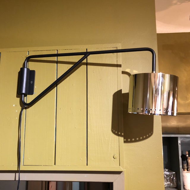 Movable swing arm, portable plug in wall lamp or sconce. Black metal arm with shiny silver metal perforated drum shade....