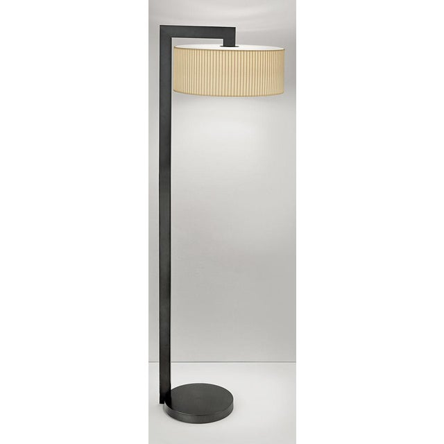 Art deco style lamp in black bronze. A circular base with a stepped detail. Linen shallow shade with an integraal LED...