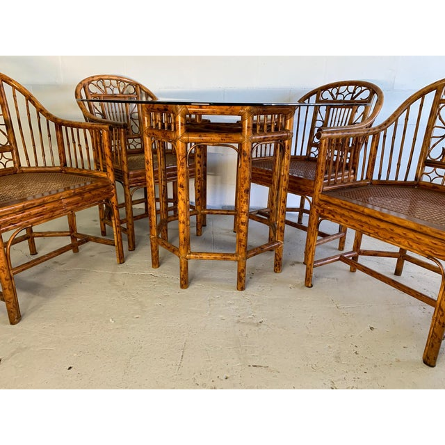 Vintage pavilion style rattan dining set by Brighton includes four chairs and matching pedestal table with glass top. Very...