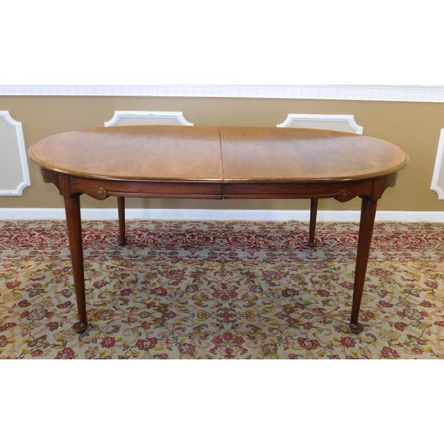 Description: This table is being sold AS IS WHERE IS. This is a decent oval dining room table with banded walnut & elm top...