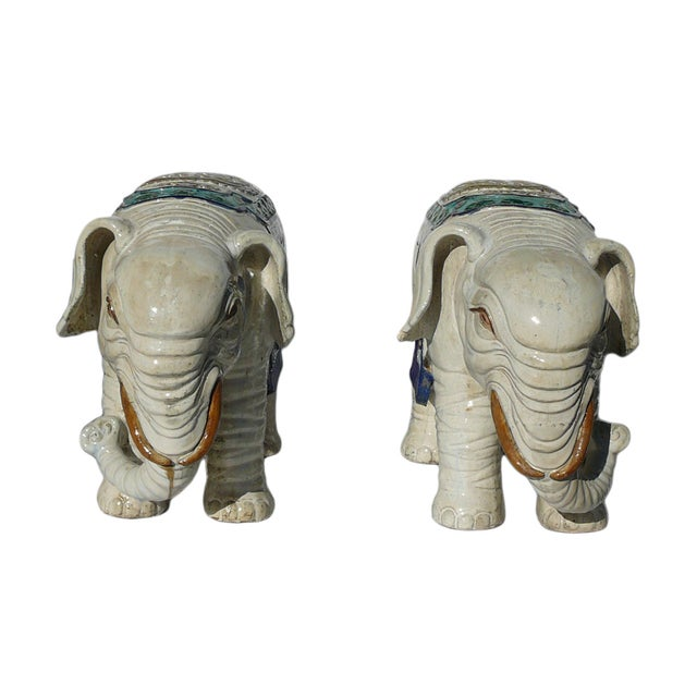 This is a pair of traditional Chinese decorative elephant figure made of ceramic and glazed with off white color. The top...