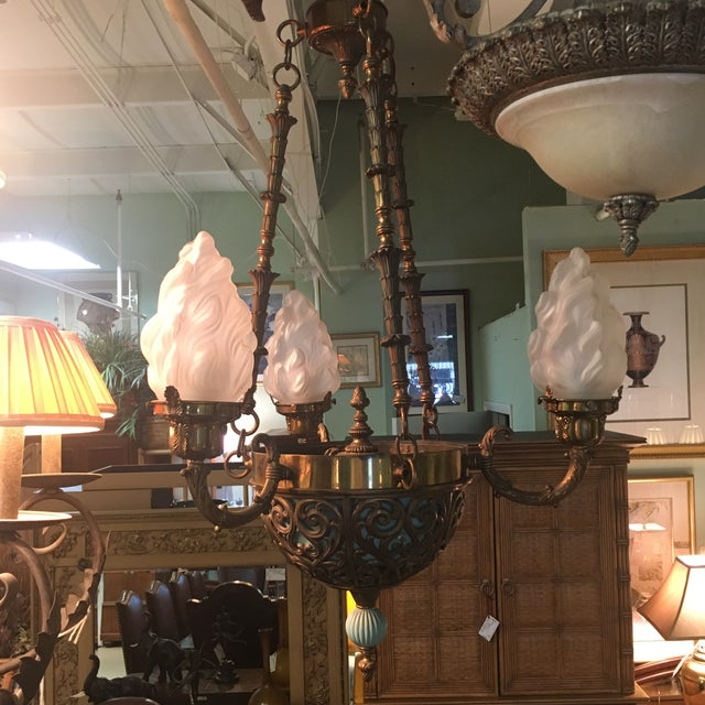 Gorgeous French art deco chandelier with three unique lalique style globes. Antique bronze and brass accent on the base....