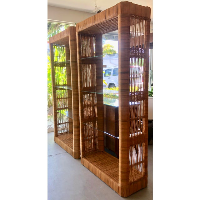 Timeless and trendy pair of rattan etageres from 70's. Each one has 4 shelves, lower in rattan and 3 in glass. Some small...