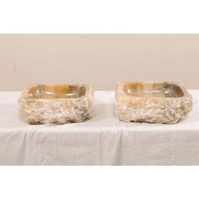A pair of natural onyx sink basins with original live edge. These carved vessel sinks, created from a rough onyx rock,...